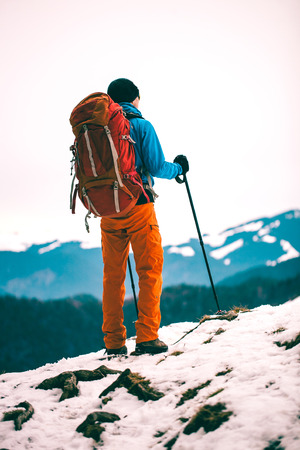 A man with backpack and trekking sticks against the backdrop of winter mountains. Climber on the top. Winter ascent in the mountains. Standard-Bild