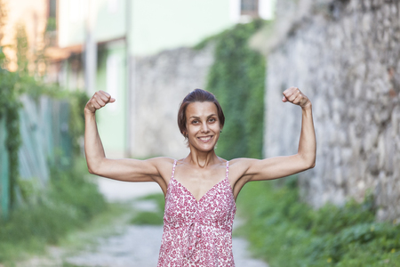 The girl shows her muscles. A woman in a summer dress shows her biceps. Strong brunette. Slender girl with strong hands.