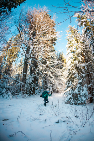 Woman with backpack and snowshoes in the winter mountains. Travel to scenic places. Blonde with trekking sticks. A tourist walks through a snowy forest. Girl walks along the path.