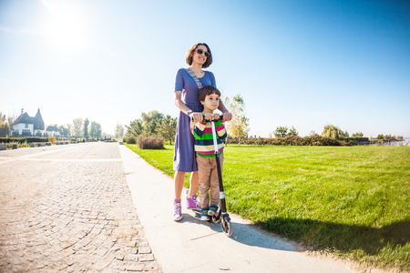 The boy with his mother rides a scooter. The child spends time with the parent in the park. A woman teaches her son to ride a scooter. Joint entertainment with parents. Standard-Bild - 115854304