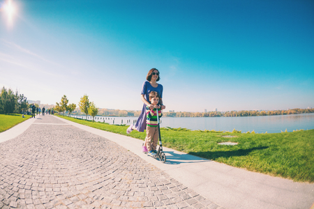 Woman riding with her son on a scooter. A boy with his mother riding in the park on a scooter. Happy holidays with parents. The girl in a dress and sneakers walks with the child. Standard-Bild - 115854373