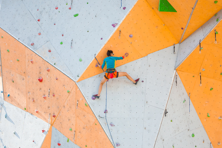 The climber trains on an artificial relief. A woman climbs a climbing route on a street climbing wall. Training in the hall. Strong girl involved in sports. Standard-Bild - 115854400