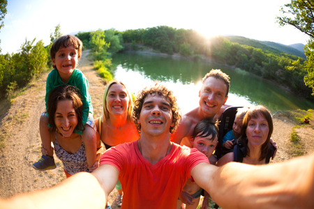 Selfie of friends on nature. Friends are resting near the lake. Great fun company. Big family gathered together on vacation. Children and parents on a picnic in the summer forest. Standard-Bild - 115854831
