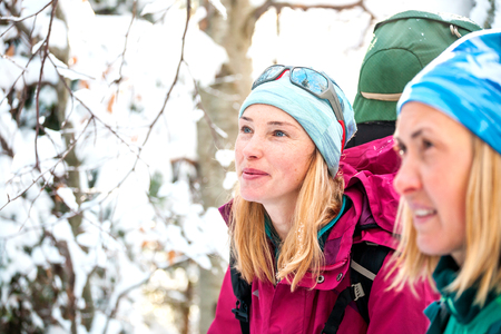 Two women in a winter hike. Girlfriends with trekking poles are on a snow covered mountain path. Girls with backpacks and snowshoes travel together. Friends walk on a sunny day through the fir forest. Standard-Bild - 115854422