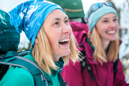 Two smiling women in a winter hike. Girlfriends with trekking poles are on a snow covered mountain path. Girls with backpacks and snow shoes travel together. Friends walk through the fir forest. Standard-Bild - 115854423