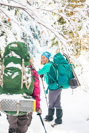 Two women in a winter hike. Girlfriends with trekking poles are on a snow covered mountain path. Girls with backpacks and snowshoes travel together. Friends walk on a sunny day through the fir forest. Standard-Bild - 115854441