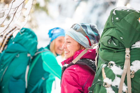 Two smiling women in a winter hike. Girlfriends with trekking poles are on a snow covered mountain path. Girls with backpacks and snow shoes travel together. Friends walk through the fir forest. Standard-Bild - 115854442