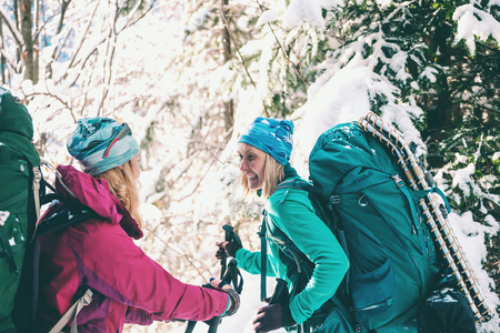 Two smiling women in a winter hike. Girlfriends with trekking poles are on a snow covered mountain path. Girls with backpacks and snow shoes travel together. Friends walk through the fir forest. Standard-Bild - 115854525