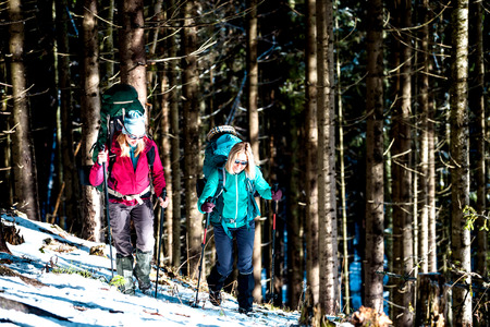 Two women in a winter hike. Girlfriends with trekking poles are on a snow covered mountain path. Girls with backpacks and snowshoes travel together. Friends walk on a sunny day through the fir forest. Standard-Bild - 115854615