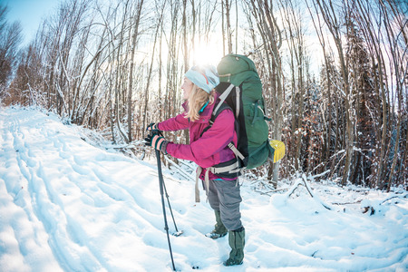 Woman in a winter hike. A girl with trekking poles, a backpack and snowshoes is walking along a snow covered mountain path. Tourist goes along the forest road. Standard-Bild - 115854835