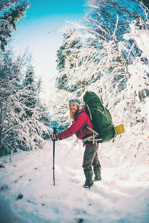 Woman with backpack and snowshoes in the winter mountains. Travel to scenic places. Blonde with trekking sticks. A tourist walks through a snowy forest. Girl walks along the path. Standard-Bild - 115854875