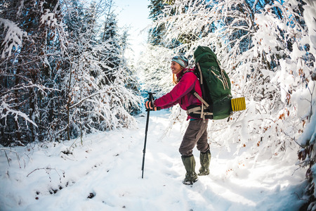 Woman with backpack and snowshoes in the winter mountains. Travel to scenic places. Blonde with trekking sticks. A tourist walks through a snowy forest. Girl walks along the path. Standard-Bild - 115854879