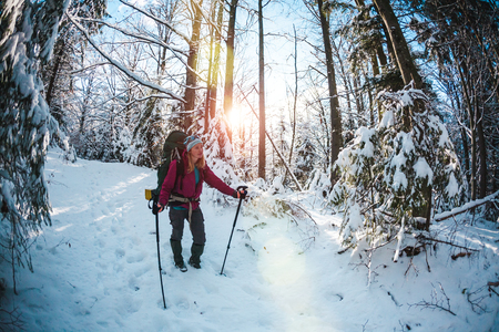 Woman with backpack and snowshoes in the winter mountains. Travel to scenic places. Blonde with trekking sticks. A tourist walks through a snowy forest. Girl walks along the path. Standard-Bild - 115854902