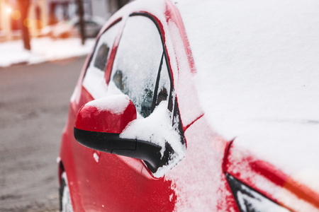 Snow covered red car. Parked vehicle close up. The machine is covered with hoarfrost. Winter snowfall. Standard-Bild - 115855228