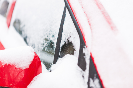 Snow covered red car. Parked vehicle close up. The machine is covered with hoarfrost. Winter snowfall. Standard-Bild - 115855245