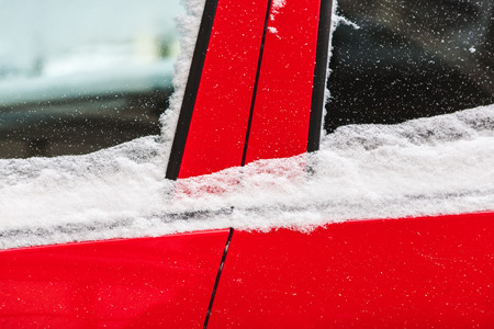 Snow covered red car. Parked vehicle close up. The machine is covered with hoarfrost. Winter snowfall. Standard-Bild - 115855246