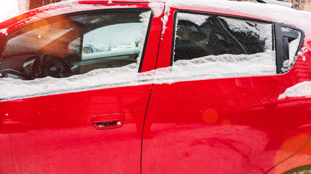 Snow covered red car. Parked vehicle close up. The machine is covered with hoarfrost. Winter snowfall. Standard-Bild - 115855262