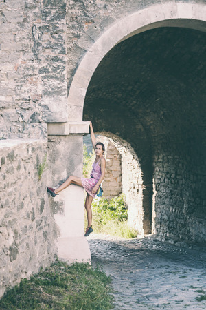 A woman in a dress is climbing a brick wall. The girl climbs on a stone fence. Climber on a city street. The wall of the old destroyed building. Standard-Bild - 115855013