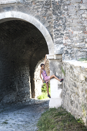 A woman in a dress is climbing a brick wall. The girl climbs on a stone fence. Climber on a city street. The wall of the old destroyed building. Standard-Bild - 115855031