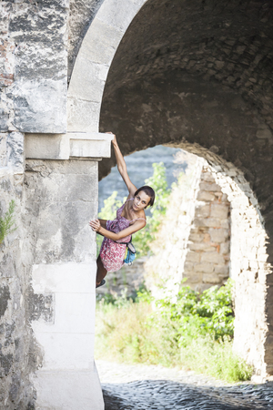 The girl climbs the stone wall. A woman in a summer dress climbs the wall of an old destroyed building. Brick fence. The climber is hanging on the city building. Strengthening the ruined castle. Standard-Bild - 115855051