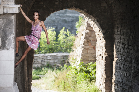 The girl climbs the stone wall. A woman in a summer dress climbs the wall of an old destroyed building. Brick fence. The climber is hanging on the city building. Strengthening the ruined castle. Standard-Bild - 115723806