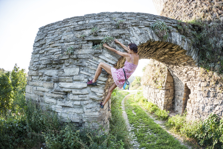A woman in a dress is climbing a brick wall. The girl climbs on a stone fence. Climber on a city street. The wall of the old destroyed building. Standard-Bild - 115723809