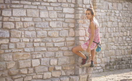 A woman in a dress is climbing a brick wall. The girl climbs on a stone fence. Climber on a city street. The wall of the old destroyed building. Standard-Bild - 115723851