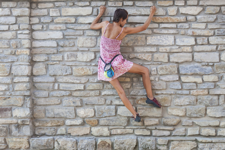 A woman in a dress is climbing a brick wall. The girl climbs on a stone fence. Climber on a city street. The wall of the old destroyed building. Standard-Bild - 115723852