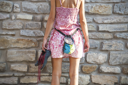 The climber is preparing to climb the stone fence. Bag for magnesia and rock shoes. A slender woman in a dress is going to climb a brick wall. Standard-Bild - 115723853