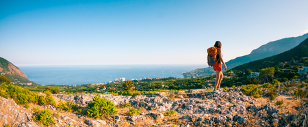 Girl at the top of the mountain. A woman with a backpack walks along a mountain path. Climb to the top. Travel to picturesque places. Tourist against the sky and the sea.