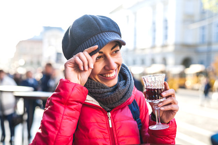 Woman holding a glass of red wine. Cherry brandy. Girl tasting alcoholic drink. Alcohol addiction. Smiling brunette in a cap walks on a city street.