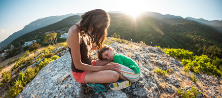 The tired boy lies on his mother's feet. A woman is traveling with her son. Tiring climb to the top of the mountain. Mom hugs the child, sitting on top of the mountain. Baby is sleeping.