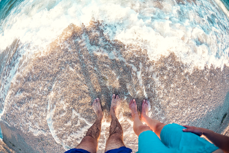 Feet in the sea. Couple on the beach. Female and male feet in the water. Ocean waves.