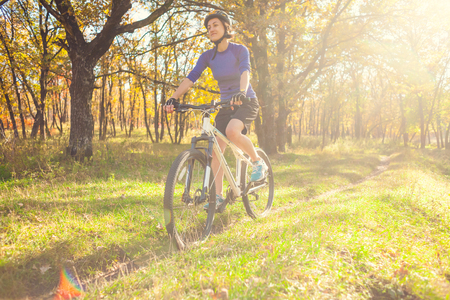 Biking in the forest. Girl rides a bike on a forest trail. Woman riding her bike in the park. Bicycle touring. Travel to scenic places. Autumn trees. Banque d'images