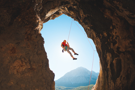 Rock climber climbs into the cave. Rock in the form of an arch. The woman trains on a natural terrain. The girl overcomes the difficult climbing route on the Turkish rocks.