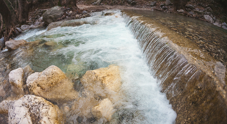Waterfall and mountain river. Clear water from melting snow. Autumn forest. River rapids. Forest stream.
