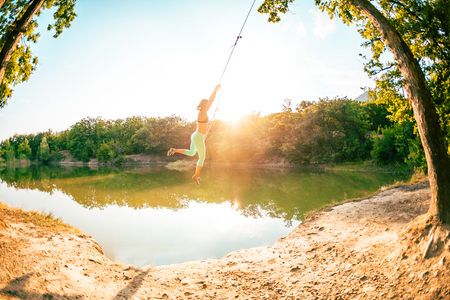 Jump into the water. A woman is resting on the lake. A swing from a rope and a stick. Active recreation in nature. Summer fun. A woman is riding a swing. Fisheye lens.