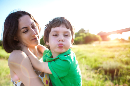 The kid is grimacing. Mother hugs the boy. A woman is walking with her son across the field. The child is sitting at mother's arms and hugs her. Mom's embrace.