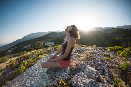 A girl is sitting on top of a mountain and smiling. A woman admires the beauty of nature. Travel to picturesque places. Tourist against the sky. The brunette looks at the horizon.
