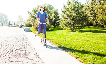 The girl rides a scooter in the park. Slim woman in dress have fun. Smiling brunette on a walk. Stock Photo