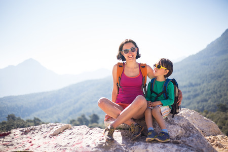 The boy and his mother are sitting on the top of the mountain. A woman travels with a child. Baby hugs mom. Travel with backpacks. Hike and climb with kids. Portrait of a woman with her son.