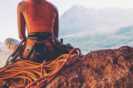 Kletterer sitzt in der Nähe des Seils und bereitet sich darauf vor, die Route zu überwinden. Schlankes Mädchen hält Kletterausrüstung. Eine Frau auf dem Hintergrund der schönen Berge. Ruhen Sie sich nach dem Klettern aus. Standard-Bild