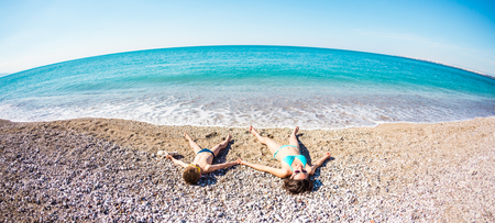 The boy with his mother sunbathe on the beach. A woman with her son are lying on the sand near the sea. Rest on the ocean coast. The child spends time with mom.