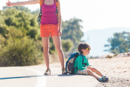 Woman with a child hitchhiking. The girl catches the car. Brunette with a backpack and young son waiting for transport. Hitchhiking in Turkey. The boy with his mother stands on a mountain road.