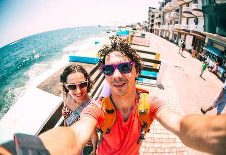 A couple takes a selfie against the backdrop of the sea. The man and the woman have a rest on the resort. Photos on the ocean coast. Lovers on the waterfront.