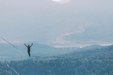 A man is walking along a stretched sling. Highline in the mountains. Man catches balance. Performance of a tightrope walker in nature. Highliner on the background of valley.