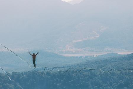 Un homme marche le long d'une écharpe tendue. Highline dans les montagnes. L'homme retrouve l'équilibre. Performance d'un funambule dans la nature. Highliner sur fond de vallée.