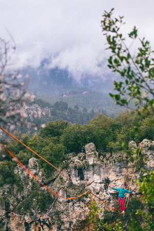 A woman is walking along a stretched sling. Highline in the mountains. Woman catches balance. Performance of a tightrope walker in nature. Highliner on the background of thunderclouds. Stock Photo