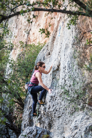 A girl climbs a rock. The athlete trains in nature. Woman overcomes difficult climbing route. Strong climber. Extreme hobby.