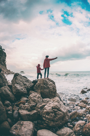 A woman with her son are standing on a stone and looking at the sea. The boy with his mother look at the waves. The child is walking along the ocean shore. Silhouette of mom and child against the sky.